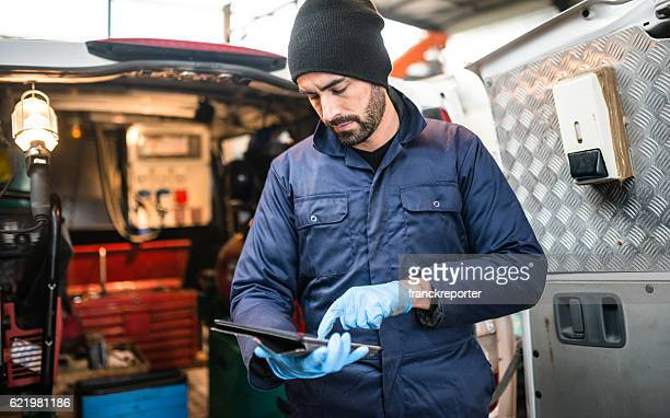 mechanic technician on a garage - mini van stock photos and pictures