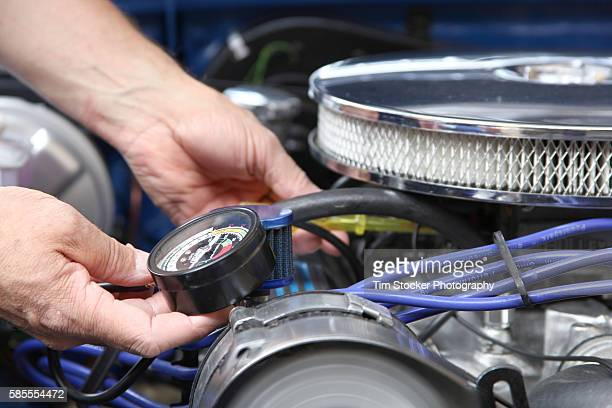 A Mechanic tuning a car engine with a vacuum gauge