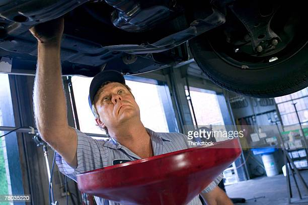 mechanic under car changing oil - oil change stock pictures, royalty-free photos & images
