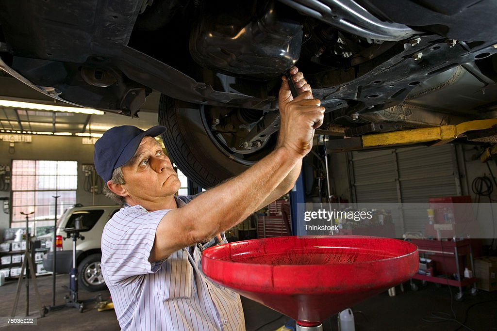 Mechanic under car changing oil : Stock Photo