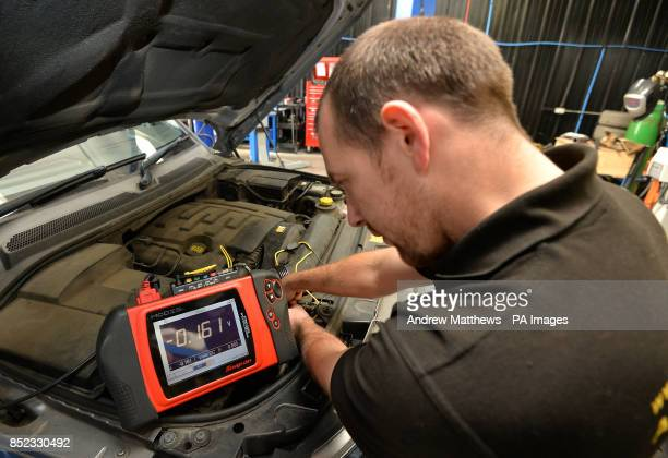 Mechanic uses a Snap-On Modis Modular Diagnostic Information System on a car's electronics