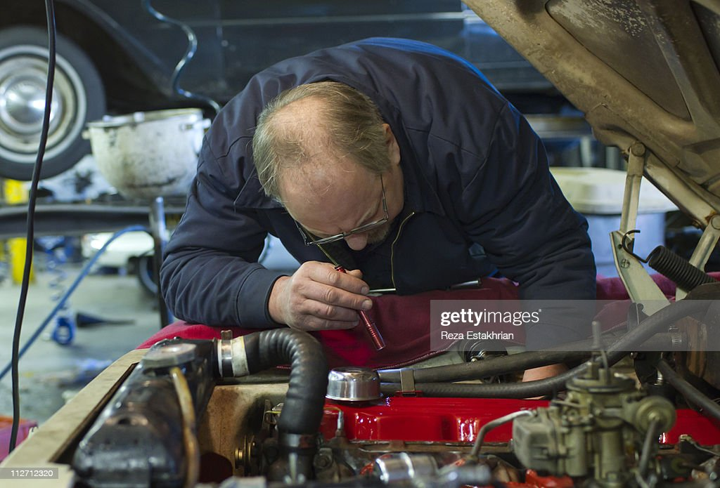 Mechanic uses flashlight to see in engine : Stock Photo