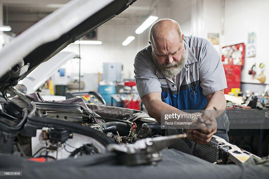 Mechanic uses force to unlock bolt : Stock Photo