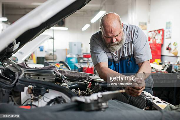 mechanic uses force to unlock bolt - mechanic stock pictures, royalty-free photos & images