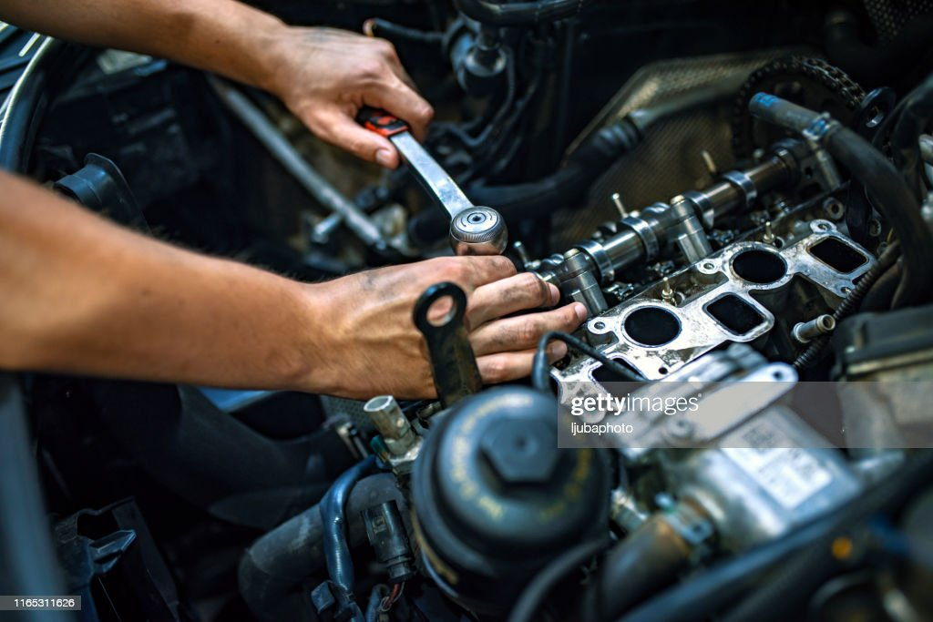 Mechanic using a ratchet wrench : Stock Photo