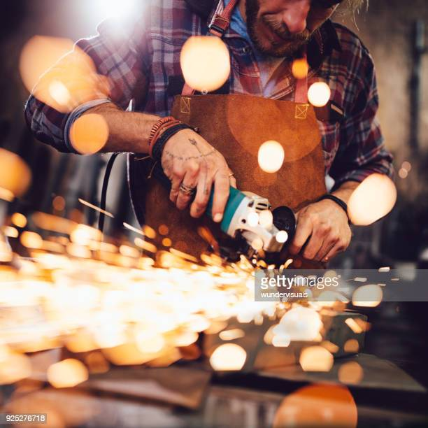 Mechanic using angle grinder and working with metal in workshop
