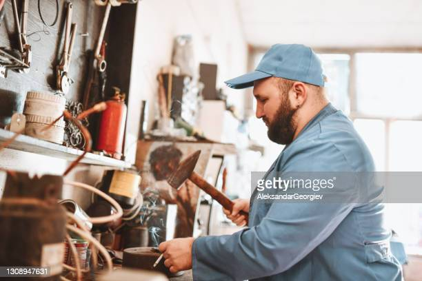 mechanic using heavy hammer to fix car part while smoking cigarette - strike industrial action stock pictures, royalty-free photos & images