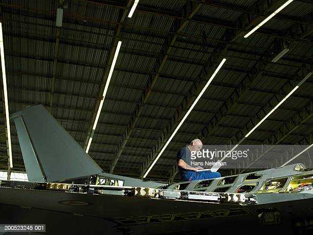 mechanic using laptop on aircraft in hangar - aerospace stock pictures, royalty-free photos & images