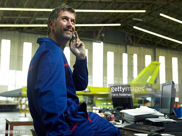 mechanic using mobile phone at desk in aircraft hanger - hans neleman ストックフォトと画像