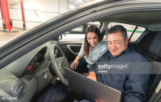 Mechanic using technology to explain car trouble to a female customer