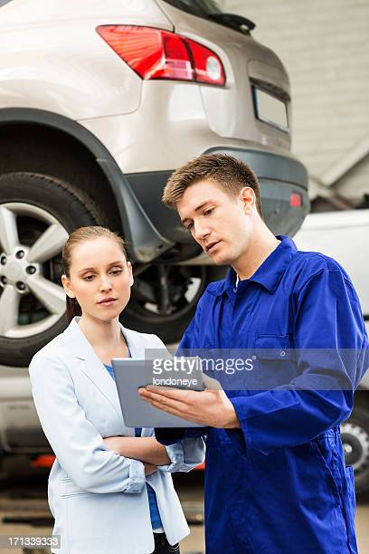 Mechanic With Customer Using Digital Tablet