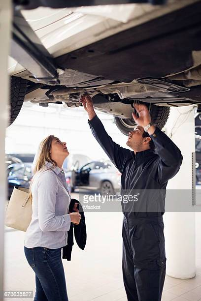 Mechanic with female customer standing under car at repair shop
