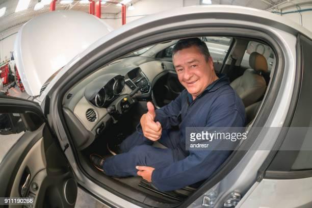 mechanic with thumbs up sitting in a car at an auto repair shop - transporte assunto imagens e fotografias de stock