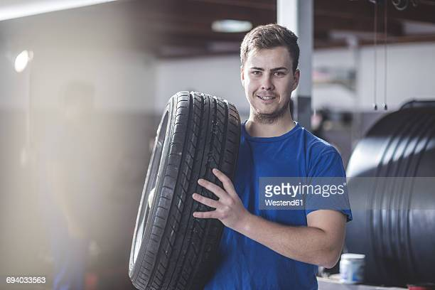 Mechanic with tyre at workshop