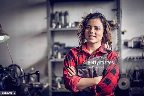 mechanic woman in workshop - weiblichkeit stock-fotos und bilder