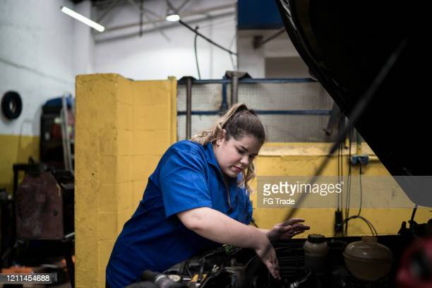 mechanic woman tidying up car in auto repair shop - conquering adversity stock pictures, royalty-free photos & images