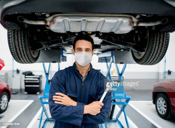mechanic working at a car garage wearing a facemask to avoid the spread of coronavirus - garage stock pictures, royalty-free photos & images