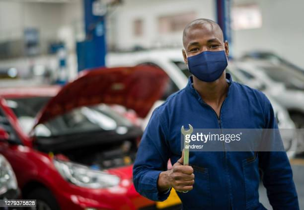 mechanic working at a garage and wearing a facemask - biosecurity stock pictures, royalty-free photos & images