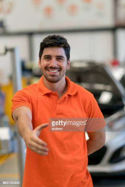 Mechanic working at a garage with hand extended for a handshake