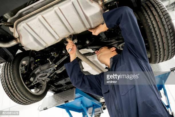 車のシャーシを見て自動車修理店で働くメカニック