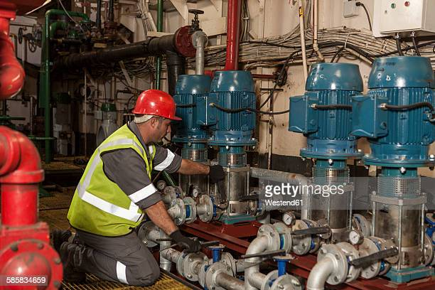 Mechanic working in engine room on a ship