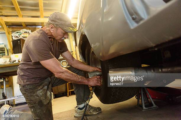mechanic working in garage shop - vintage auto repair stock pictures, royalty-free photos & images