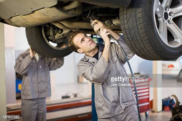 Mechanic working on car engine in garage