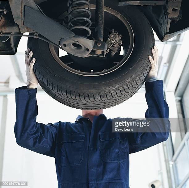mechanic working on car, face obscured by wheel, low angle view - blue jumpsuit stock pictures, royalty-free photos & images