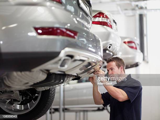 mechanic working on car in auto repair shop - bumper stock pictures, royalty-free photos & images