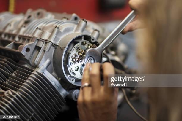 Mechanic working on motorcycle engine in workshop