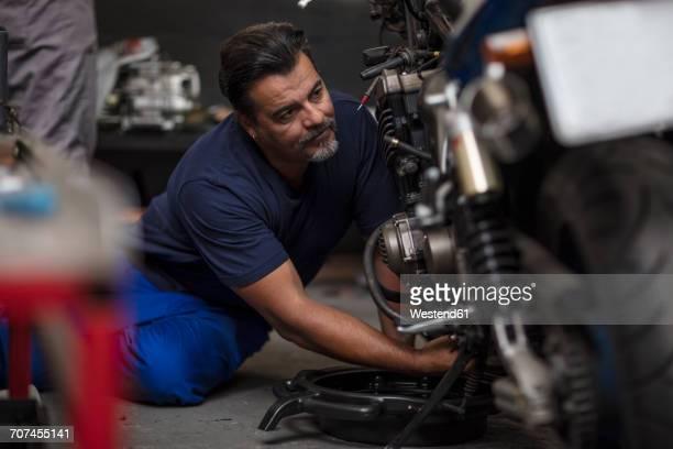 Mechanic working on motorcycle in workshop