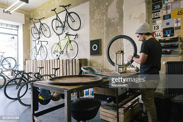 Mechanic working on tire in a custom-made bicycle store