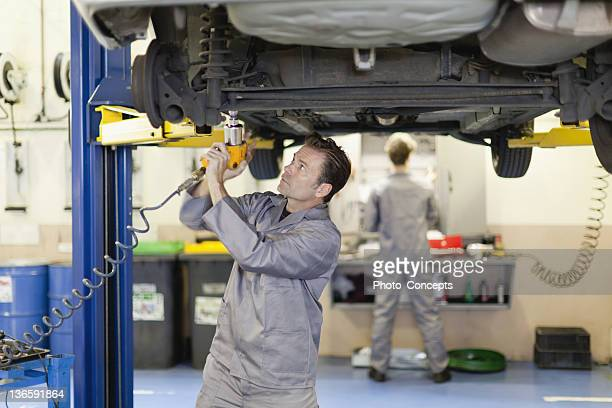 Mechanic working on underside of car