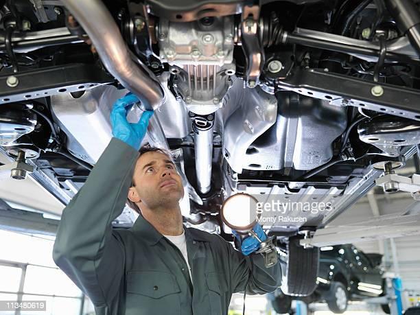 Mechanic working under car in car dealership workshop holding torch