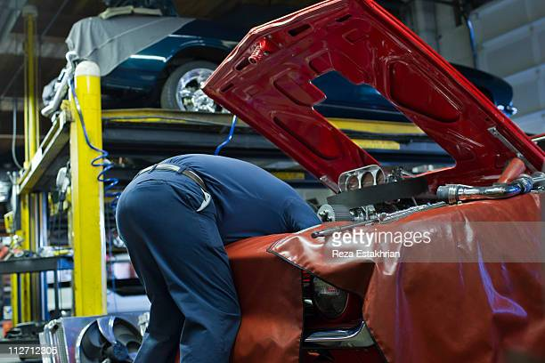Mechanic works deep inside engine
