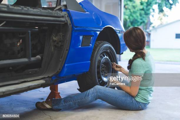 mechanic works on car in her home garage - rally car stock photos and pictures