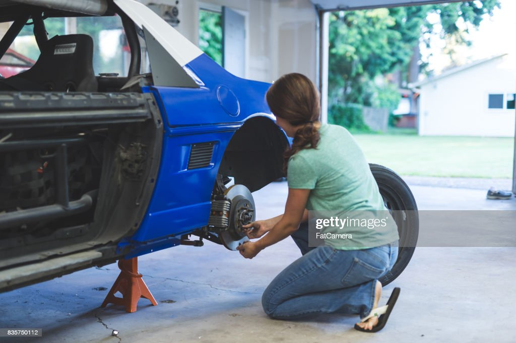 Mechanic works on car in her home garage : Stock Photo