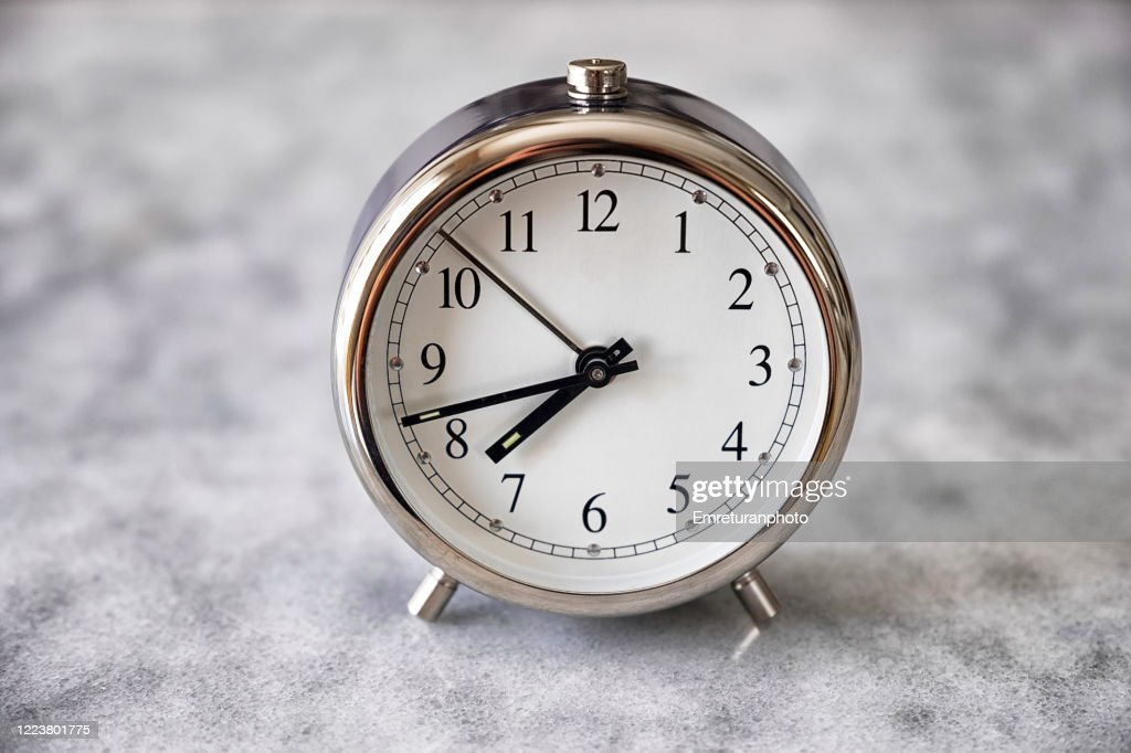 Mechanical alarm clock on gray marble table top : Stock Photo