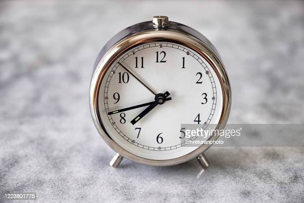 mechanical alarm clock on gray marble table top - emreturanphoto stock pictures, royalty-free photos & images