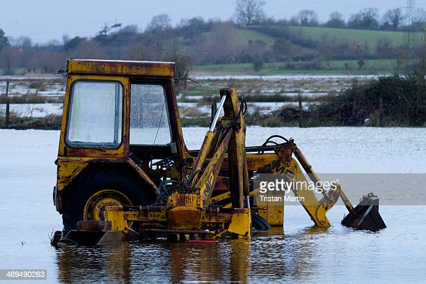Mechanical digger lies abandoned to the floodwaters on the Somerset Levels near Burowbridge in Somerset, England. Large areas of the Somerset Levels...