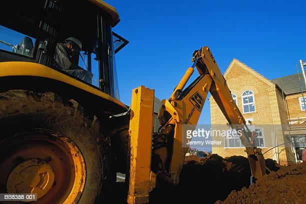 mechanical digger on construction site, england - excavator - fotografias e filmes do acervo