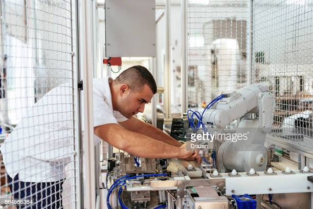 mechanical engineer setting up robotic arm in factory - ergonomics stock photos and pictures