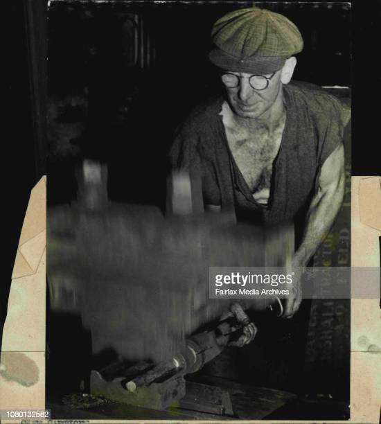"""Mechanical hammer belting a red-hot solid steel cylinder into the rough shape of an Owen Gun barrel at a munitions factory """"somewhere in NSW"""". The..."""