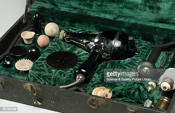 Mechanical masseur motor head with various vibratory attachments in wooden cloth covered carrying case made by General Electric Co