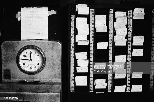 A mechanical time clock and a rack of time cards at Stockwell Bus Garage south London 26th February 1967