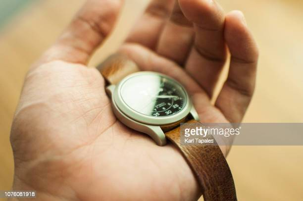 a mechanical watch held by human hand - wrist watch stock pictures, royalty-free photos & images
