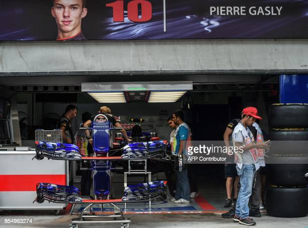 TOPSHOT Mechanics assemble Toro Rosso's French driver Pierre Gasly's car ahead of the Formula One Malaysia Grand Prix in Sepang on September 28 2017...