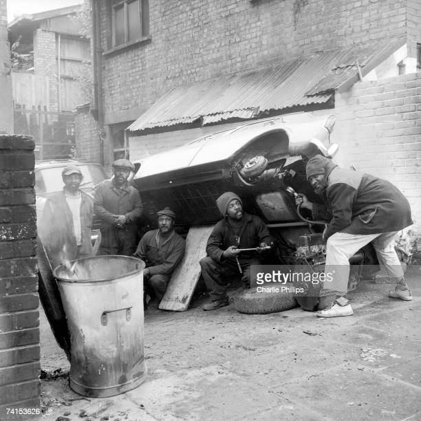 Mechanics at a car repair shop on Acklam Road in the Notting Hill area of London, 1969.