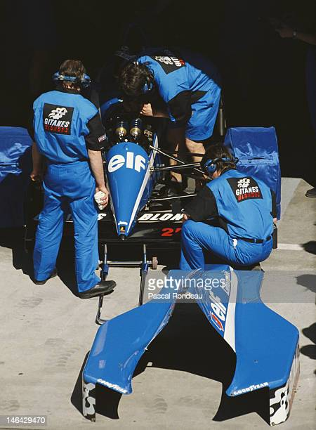 Mechanics at work on the Ligier Gitanes Ligier JS35 Lamborghini V12 of Thierry Boutsen of Belgium during practice for the Iceberg United States Grand...