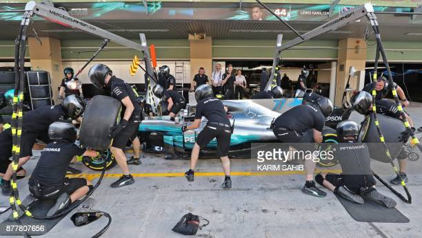 Mechanics change tires for Mercedes' Finnish driver Valtteri Bottas at the pit of the Abu Dhabi Formula One Grand Prix at Yas Marina Circuit in Abu...